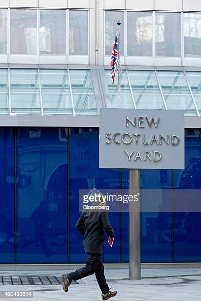 A pedestrian runs past a revolving sign outside New Scotland Yard the headquarters of London's Metropolitan Police Service in London UK on Monday Dec...