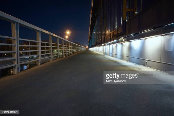 Pedestrian section of a large bridge over Moskva river at night