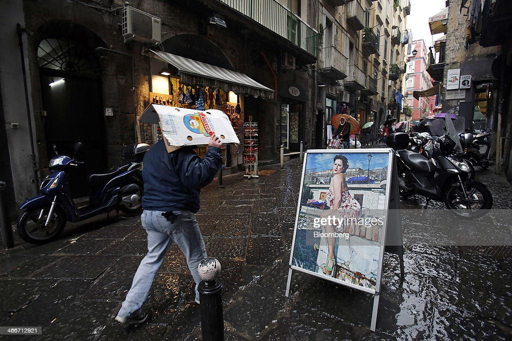 A pedestrian shelters from the rain beneath a folded cardboard box as he passes an advertisement for a photographer's studio in Naples, Italy, on Saturday, Feb. 1, 2014. In Naples, the local youth unemployment rate in 2012 was 53.6 percent compared to a national average of 35.3 percent. Photographer: Alessia Pierdomenico/Bloomberg via Getty Images