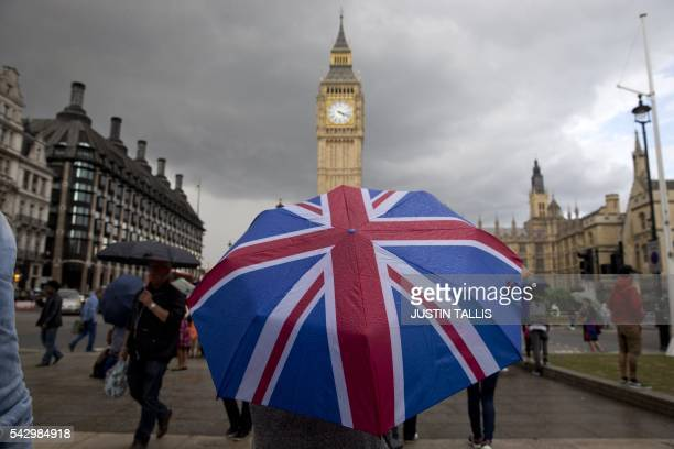 TOPSHOT A pedestrian shelters from the rain beneath a Union flag themed umbrella as they walk near the Big Ben clock face and the Elizabeth Tower at...
