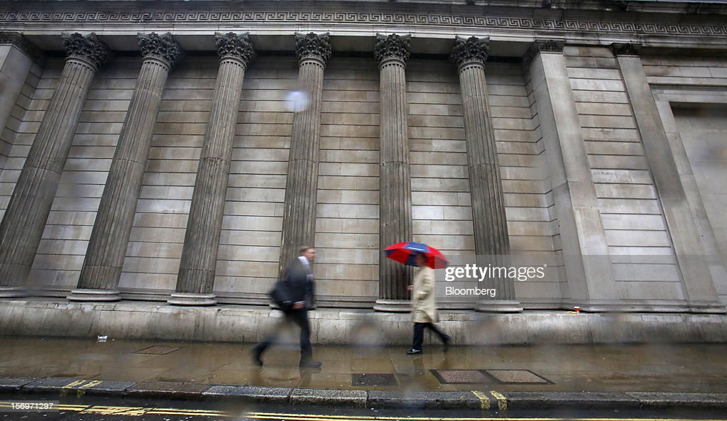 A pedestrian shelters from the rain beneath an umbrella as he passes the Bank of England (BOE), in London, U.K., on Friday, Nov. 23, 2012. Bank of Canada Governor Mark Carney was unexpectedly appointed as the next head of the Bank of England, succeeding Mervyn King. Photographer: Simon Dawson/Bloomberg via Getty Images