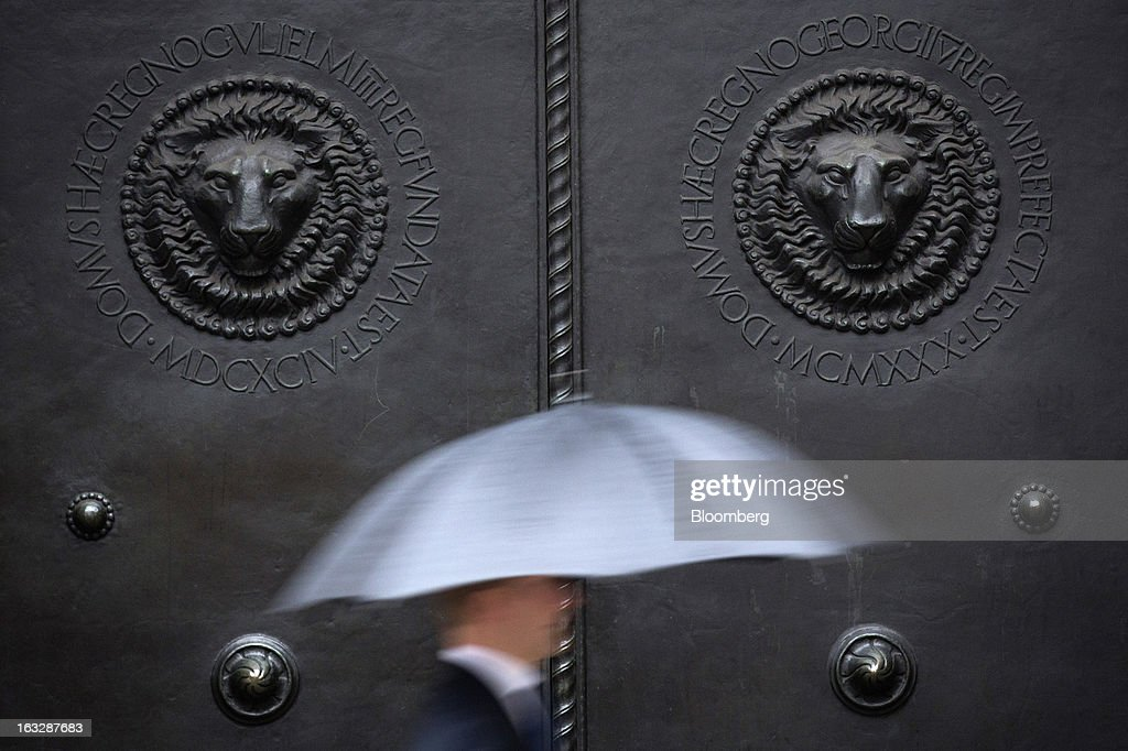 A pedestrian shelters from the rain beneath an umbrella as he passes the closed main doors of the Bank of England (BoE) in London, U.K., on Thursday, March 7, 2013. The pound dropped to its weakest level in more than 2 1/2 years versus the dollar before Bank of England policy makers announce their decision on whether they will add more stimulus to boost the U.K. economy. Photographer: Simon Dawson/Bloomberg via Getty Images
