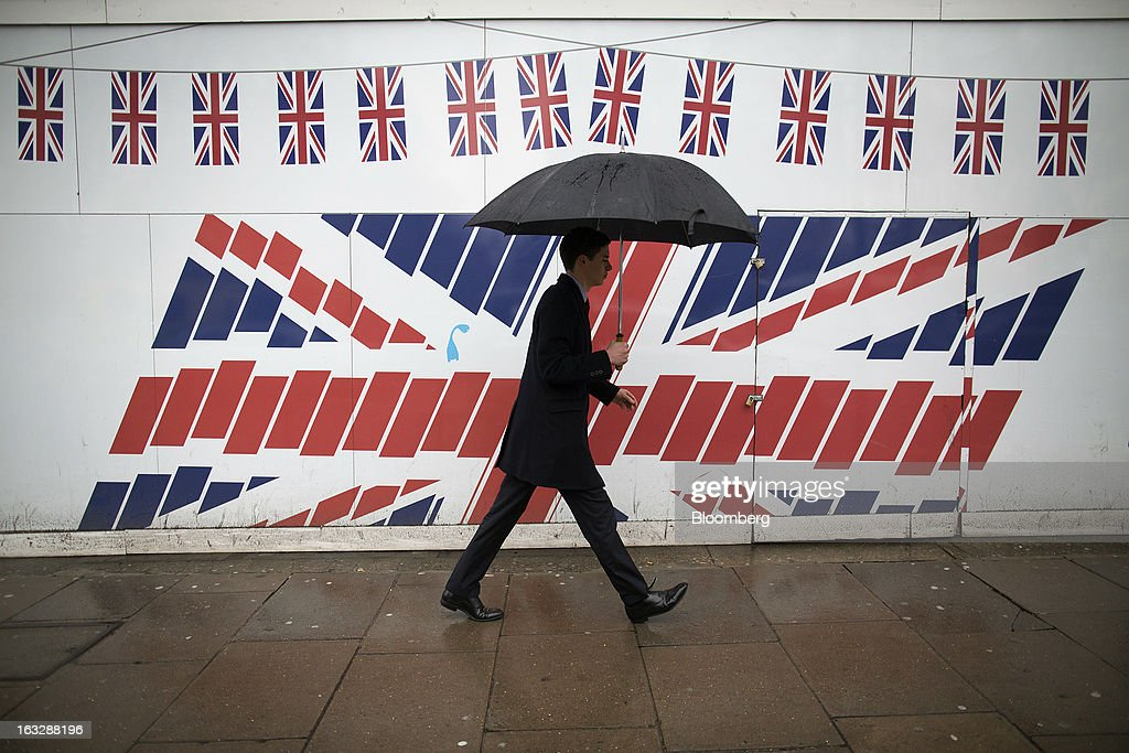 A pedestrian shelters from the rain beneath an umbrella as he passes construction hoardings decorated with British Union Jack flags in London, U.K., on Thursday, March 7, 2013. The pound dropped to its weakest level in more than 2 1/2 years versus the dollar before Bank of England policy makers announce their decision on whether they will add more stimulus to boost the U.K. economy. Photographer: Simon Dawson/Bloomberg via Getty Images