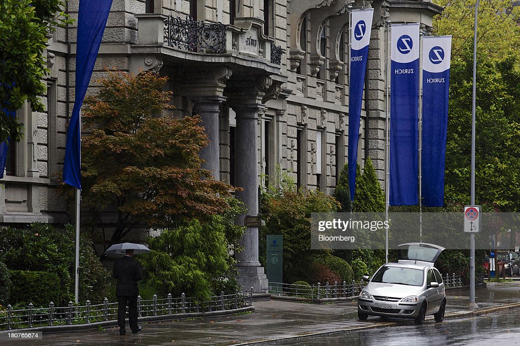 A pedestrian shelters from the rain beneath an umbrella as he walks past Zurich Insurance Group AG's headquarters in Zurich, Switzerland, on Monday, Sept. 16, 2013. Zurich Insurance named Tom de Swaan chairman, replacing Josef Ackermann, who stepped down after the suicide of Chief Financial Officer Pierre Wauthier. Photographer: Gianluca Colla/Bloomberg via Getty Images