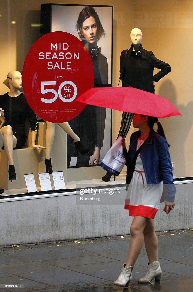 A pedestrian shelters from the rain beneath an umbrella as she looks at a sale sign in the window of a clothes store in Manchester, U.K., on Thursday, Sept. 3, 2013. U.K. consumer confidence rose to the highest in almost six years in September as signs of a sustainable economic recovery spurred consumers to spend. Photographer: Paul Thomas/Bloomberg via Getty Images