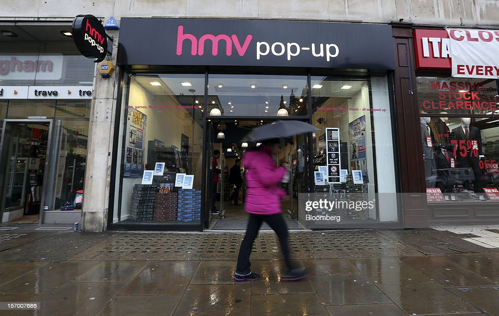 A pedestrian shelters from the rain beneath an umbrella as she passes a HMV pop-up store in London, U.K., on Tuesday, Nov. 27, 2012. Fashion chain Hobbs is among those that have opened pop-up stores for the first time this year, while CD and DVD retailer HMV Group Plc is adding more than usual for the holiday in an effort to win business. Photographer: Chris Ratcliffe/Bloomberg via Getty Images