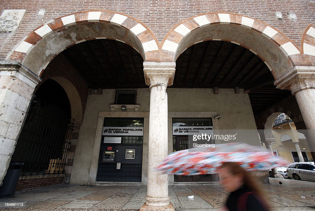 A pedestrian shelters from the rain beneath an umbrella as she passes a branch of Banca Popolare di Verona bank, a subsidiary of Banco Popolare SC, in Verona, Italy, on Monday, March 25, 2013. Italy's economy remains mired in its longest recession in two decades and a month-old political impasse threatens to increase sovereign-debt yields and bank funding costs. Photographer Alessia Pierdomenico/Bloomberg via Getty Images