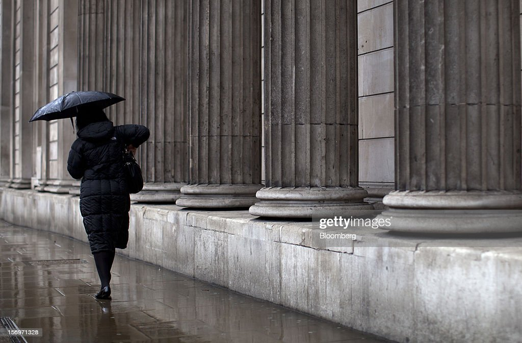 A pedestrian shelters from the rain beneath an umbrella as she passes the Bank of England (BOE), in London, U.K., on Friday, Nov. 23, 2012. Bank of Canada Governor Mark Carney was unexpectedly appointed as the next head of the Bank of England, succeeding Mervyn King. Photographer: Simon Dawson/Bloomberg via Getty Images