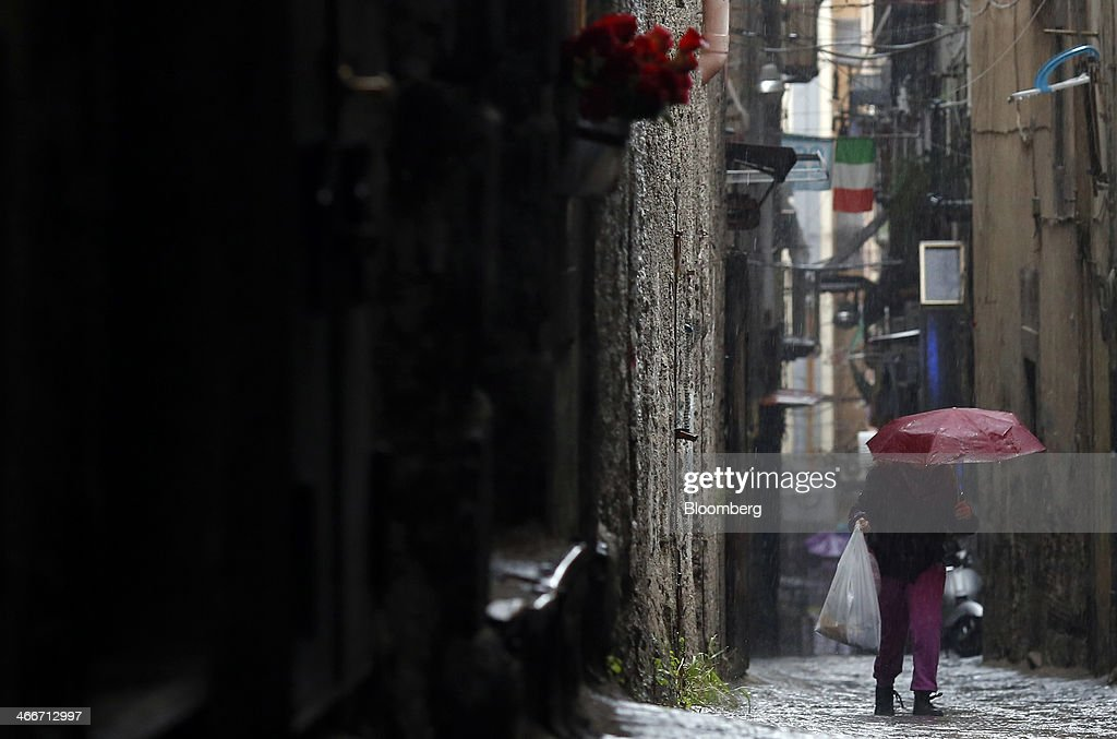A pedestrian shelters from the rain beneath an umbrella as she walks along a side street in Naples, Italy, on Saturday, Feb. 1, 2014. In Naples, the local youth unemployment rate in 2012 was 53.6 percent compared to a national average of 35.3 percent. Photographer: Alessia Pierdomenico/Bloomberg via Getty Images