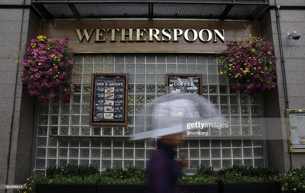 A pedestrian shelters from the rain beneath an umbrella as they walk past a JD Wetherspoon Plc pub in London, U.K., on Friday, Sept. 13, 2013. JD Wetherspoon, who reported full year sales today, are planning to move into the Irish market next year, Chairman Tim Martin said in a recent interview. Photographer: Matthew Lloyd/Bloomberg via Getty Images
