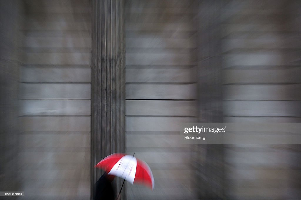 A pedestrian shelters from the rain beneath an umbrella while passing the Bank of England (BoE) in London, U.K., on Thursday, March 7, 2013. The pound dropped to its weakest level in more than 2 1/2 years versus the dollar before Bank of England policy makers announce their decision on whether they will add more stimulus to boost the U.K. economy. Photographer: Simon Dawson/Bloomberg via Getty Images