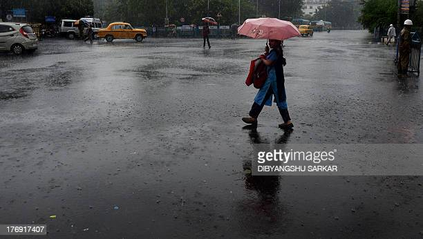 A pedestrian shelters under an umbrella as she crosses the street in Kolkata on August 19 2013The monsoon season which runs from June to September...