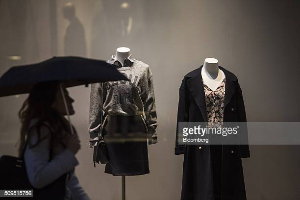 A pedestrian shelters under an umbrella as they pass a Claudie Pierlot luxury clothing store operated by SMCP Group in Toulouse France on Wednesday...