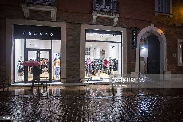A pedestrian shelters under an umbrella as they pass a Sandro luxury clothing store operated by SMCP Group at night in Toulouse France on Wednesday...