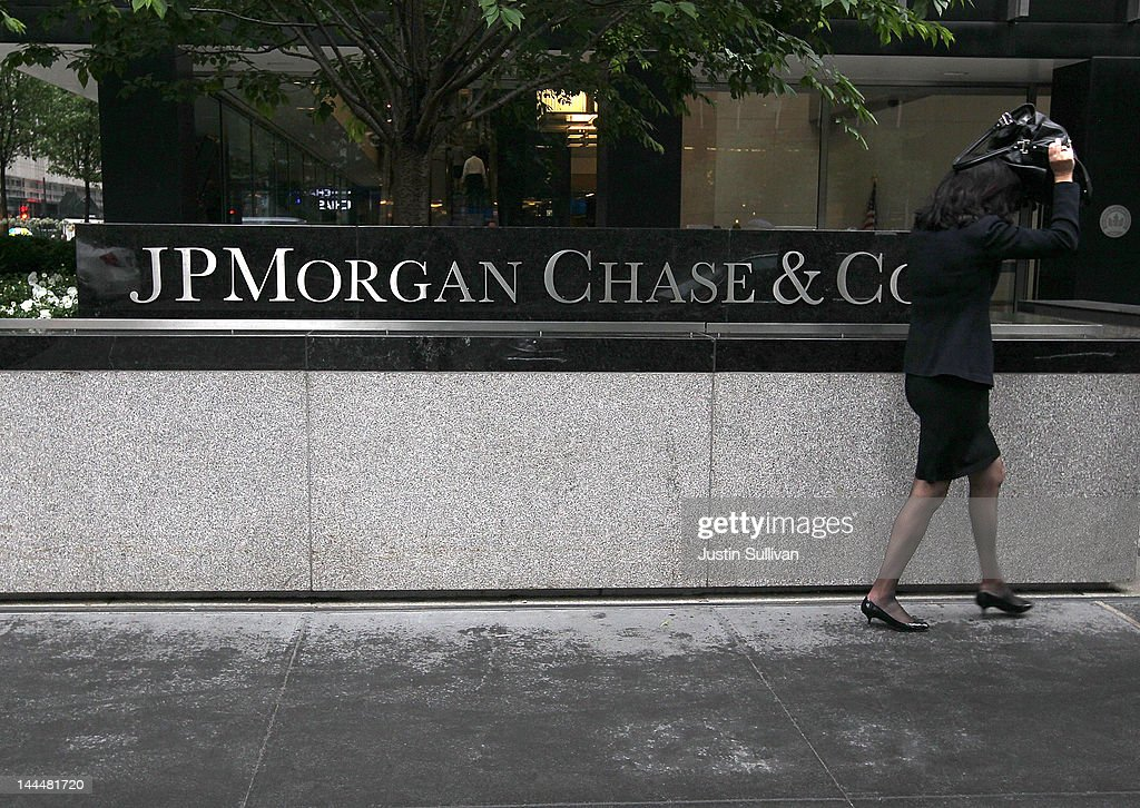 A pedestrian shields herself from the rain by a sign outside of the JPMorgan Chase headquarters on May 14, 2012 in New York City. Following a $2 billion trading blunder, JPMorgan Chase's chief investment officer Ina Drew retired and will be succeeded by Matt Zames, an executive from JPMorgan's investment bank. At least two others are also being held accountable for the mistake.