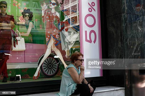 A pedestrian sits and smokes a cigarette outside a store window advertising 50% discounts during the summer sales in Athens Greece on Monday July 13...