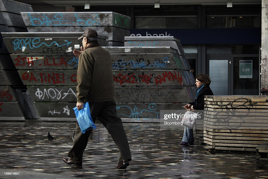 A pedestrian sits and smokes near a graffiti-covered wall on a street in Athens, Greece, on Thursday, Jan. 24, 2013. Greece's government has implemented budget cuts and economic reforms to tame a fiscal deficit that has led to bailouts from the European Union and the International Monetary Fund. Photographer: Kostas Tsironis/Bloomberg via Getty Images
