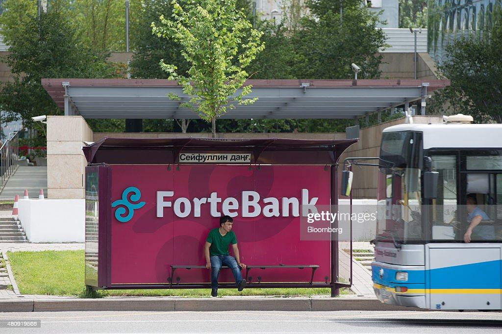 A pedestrian sits in a bus shelter advertising ForteBank JSC as he waits for public transport in Almaty Kazakhstan on Sunday June 28 2015 Almaty with...