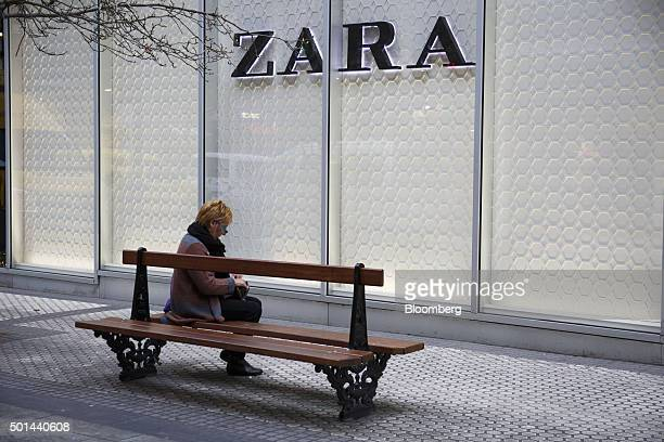 A pedestrian sits on a street bench outside a Zara fashion store operated by Inditex SA in San Sebastian Spain on Tuesday Dec 15 2015 Spain is facing...