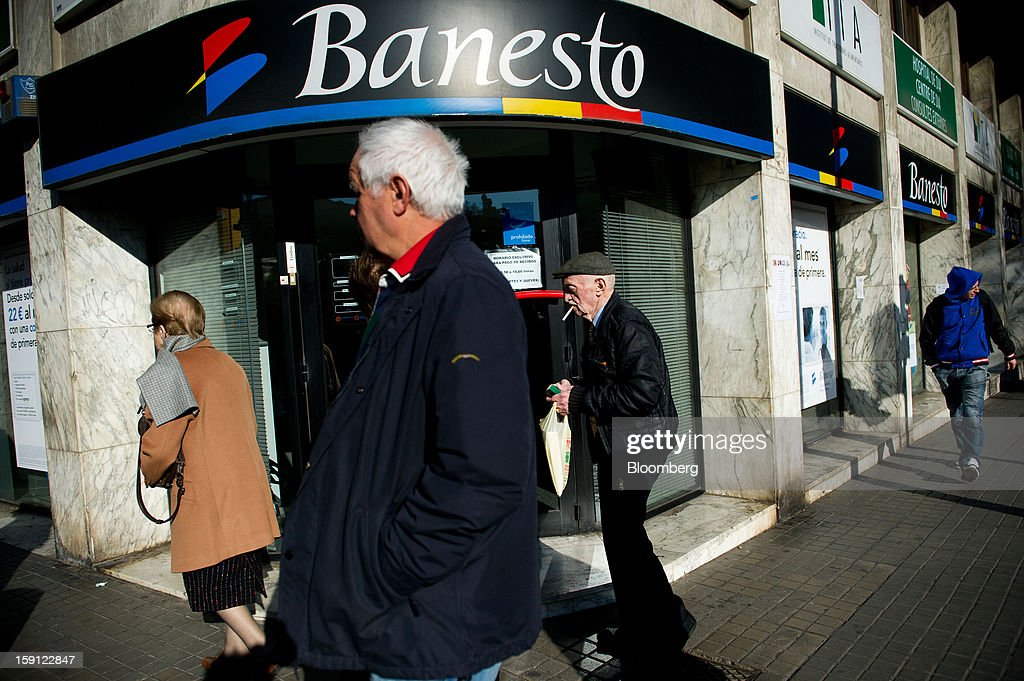 A pedestrian smokes a cigarette while passing a Banesto logo above the entrance to a Banco Espanol de Credito SA bank branch in Barcelona, Spain, on Tuesday, Jan. 8, 2013. Banco Santander SA, Spain's biggest lender, will offer 263 million euros ($345 million) in stock to buy out minority investors in its Banco Espanol de Credito SA retail unit and close 700 local branches to cut costs. Photographer: David Ramos/Bloomberg via Getty Images