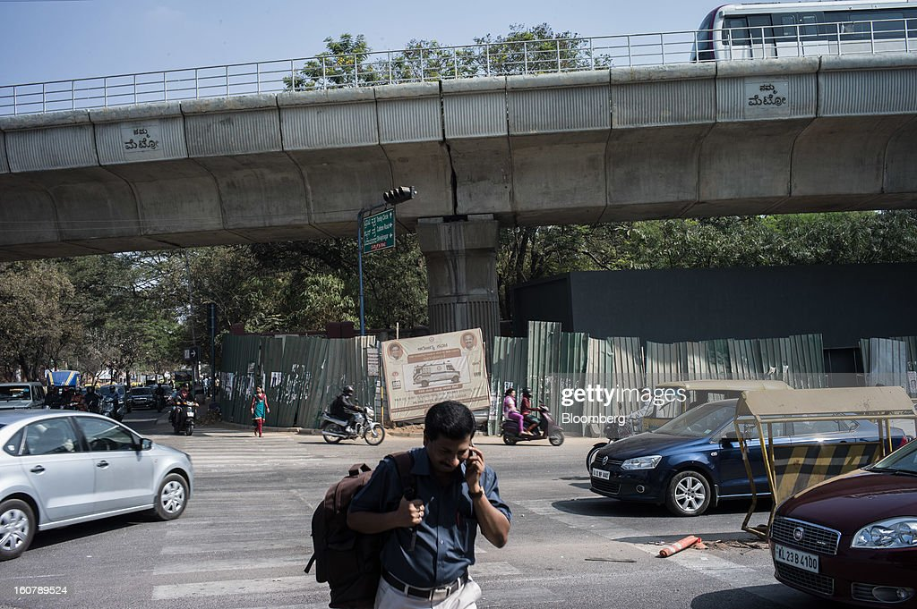 A pedestrian speaking on a mobile phone crosses the road in front of a Bangalore Metro Rail Corp. (BMRCL) train track in Bangalore, India, on Tuesday, Feb. 5, 2013. India's monetary authority predicted that the economy will expand 5.5 percent in the year ending March 31, which would be the smallest gain since 2003. Photographer: Sanjit Das/Bloomberg via Getty Images