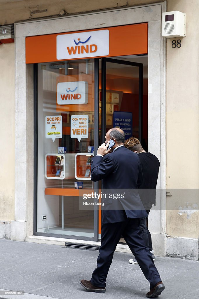 A pedestrian speaks on a mobile handset as he passes a Wind SpA mobile phone store, owned by VimpelCom Ltd., in Rome, Italy, on Thursday, April 4, 2013. Italy's state-owned postal service and Wind SpA, the country's third-largest mobile-phone company, are discussing a possible venture with Wind's fixed-line network Infostrada, Poste Italiane SpA Chief Executive Officer Massimo Sarmi said. Photographer: Alessia Pierdomenico/Bloomberg via Getty Images