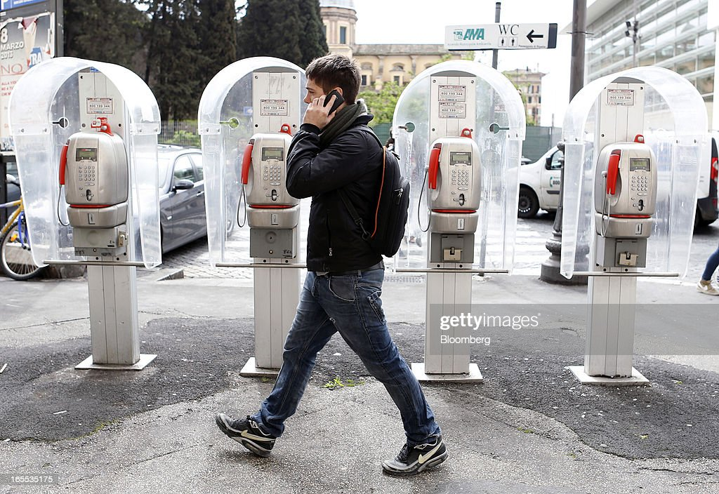 A pedestrian speaks on a mobile handset as he passes public payphones operated by Telecom Italia SpA in Rome, Italy, on Thursday, April 4, 2013. Italy's state-owned postal service and Wind SpA, the country's third-largest mobile-phone company, are discussing a possible venture with Wind's fixed-line network Infostrada, Poste Italiane SpA Chief Executive Officer Massimo Sarmi said. Photographer: Alessia Pierdomenico/Bloomberg via Getty Images