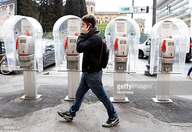 A pedestrian speaks on a mobile handset as he passes public payphones operated by Telecom Italia SpA in Rome Italy on Thursday April 4 2013 Italy's...