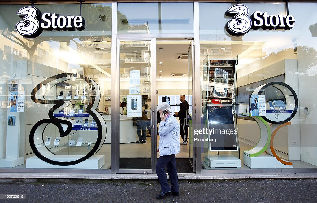 A pedestrian speaks on a mobile handset as she passes a 3 Italia mobile phone store in Rome, Italy, on Monday, April 15, 2013. Telecom Italia SpA, which received approval from its board to pursue a possible merger with Hutchison Whampoa Ltd.'s Italian business 3 Italia, said billionaire Li Ka-shing's company would want control of any combined entity. Photographer Alessia Pierdomenico/Bloomberg via Getty Images