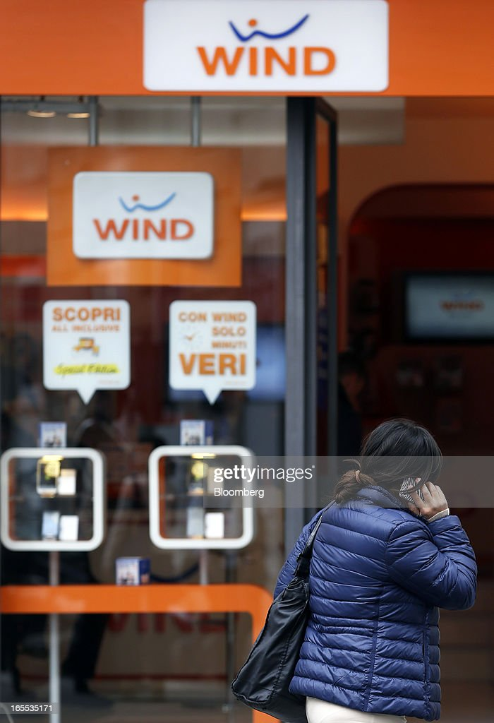A pedestrian speaks on a mobile handset as she passes a Wind SpA mobile phone store, owned by VimpelCom Ltd., in Rome, Italy, on Thursday, April 4, 2013. Italy's state-owned postal service and Wind SpA, the country's third-largest mobile-phone company, are discussing a possible venture with Wind's fixed-line network Infostrada, Poste Italiane SpA Chief Executive Officer Massimo Sarmi said. Photographer: Alessia Pierdomenico/Bloomberg via Getty Images