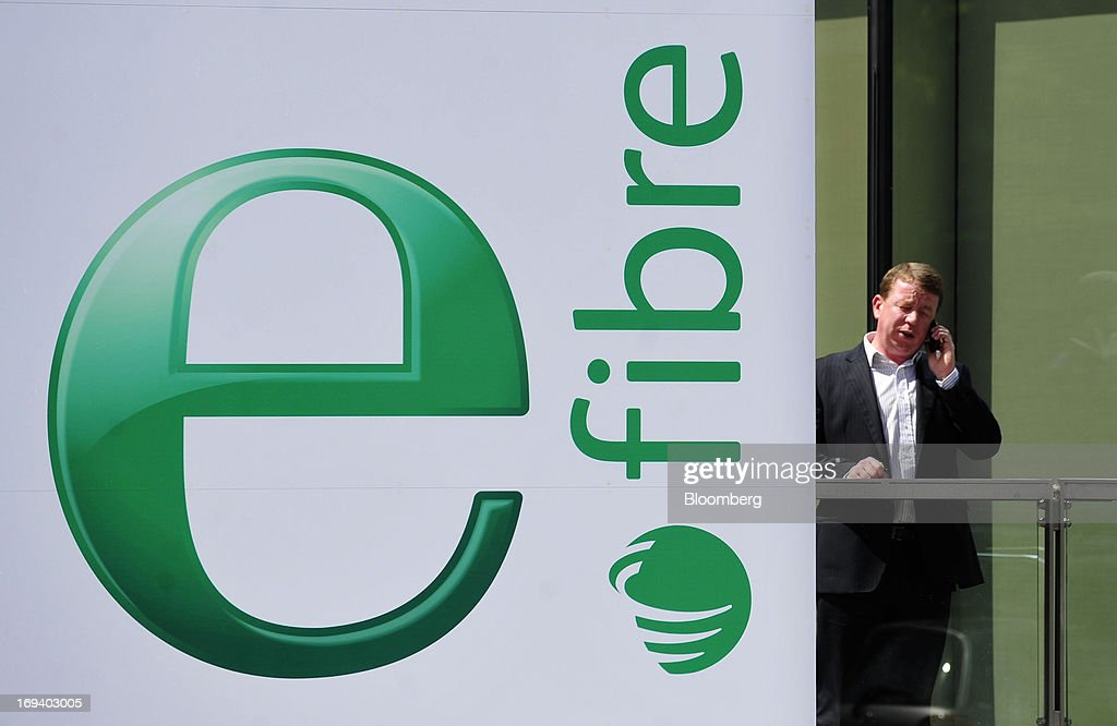 A pedestrian speaks on a mobile handset near an advert for Eircom Group's new eFibre broadband product outside the company's headquarters in Dublin, Ireland, on Thursday, May 23, 2013. Eircom Group, which has changed ownership six times since 1999, 'would like to be consolidators rather than consolidated' amid expected mergers and acquisitions in the Irish telecoms market, its Chief Financial Officer Richard Moat said. Photographer: Aidan Crawley/Bloomberg via Getty Images