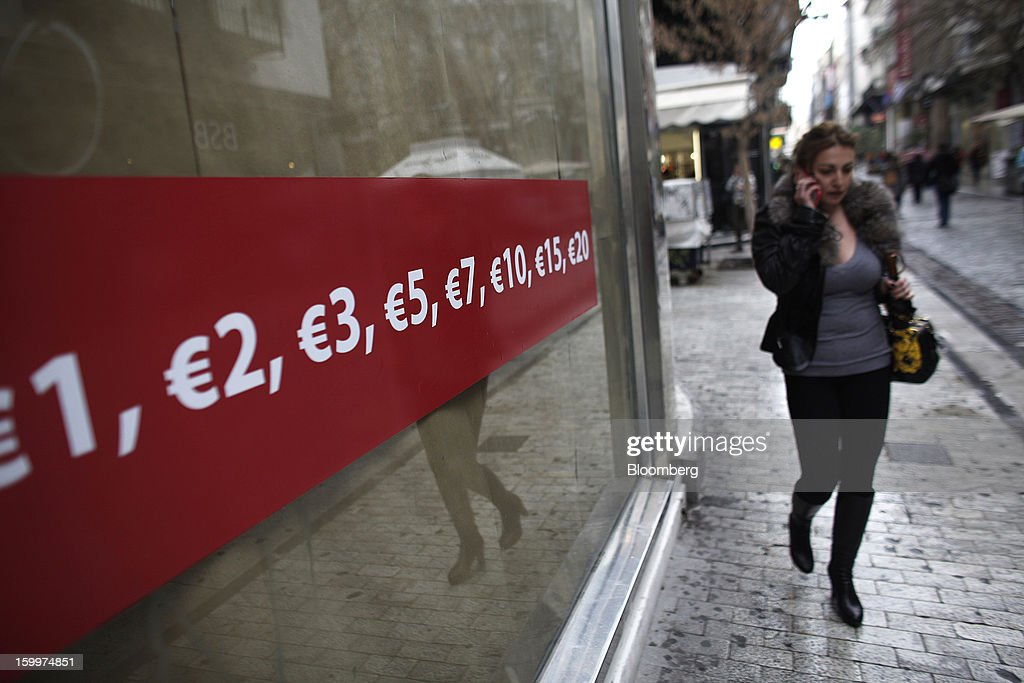 A pedestrian speaks on a mobile phone while passing a euro price sales advertisement in the window of a store in Athens, Greece, on Thursday, Jan. 24, 2013. Greece's government has implemented budget cuts and economic reforms to tame a fiscal deficit that has led to bailouts from the European Union and the International Monetary Fund. Photographer: Kostas Tsironis/Bloomberg via Getty Images