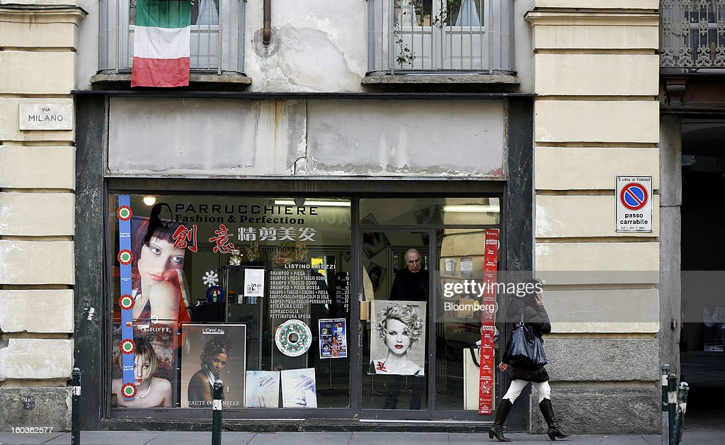 A pedestrian speaks on her mobile phone as she passes a hairdresser's shop in Turin, Italy, on Tuesday, Jan. 29, 2013. Italy sold 8.5 billion euros ($11.4 billion) of six-month Treasury bills as rates dropped to the lowest in almost three years as the European Central Bank's pledge to buy bonds continues to provide an effective backstop even amid rising political concerns. Photographer: Alessia Pierdomenico/Bloomberg via Getty Images