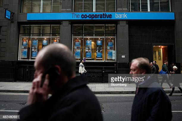 A pedestrian speaks on his mobile phone as he walks past a CoOperative Bank Plc bank branch in London UK on Friday Nov 29 2013 CoOperative Bank Plc...