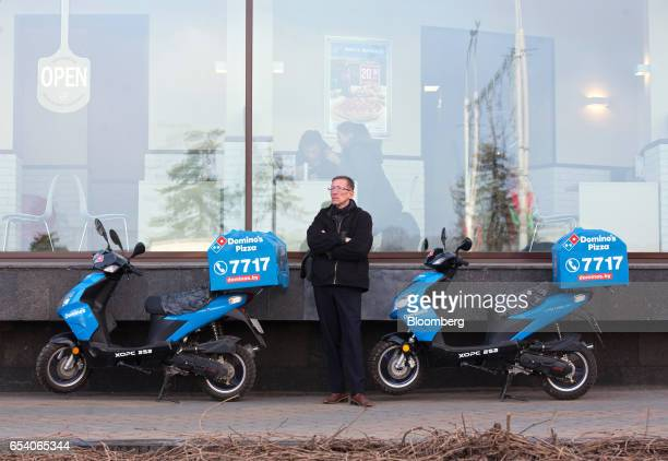 A pedestrian stands between food delivery scooters outside a Domino's Pizza Inc restaurant in Minsk Belarus on Wednesday March 15 2017 Belarusian...