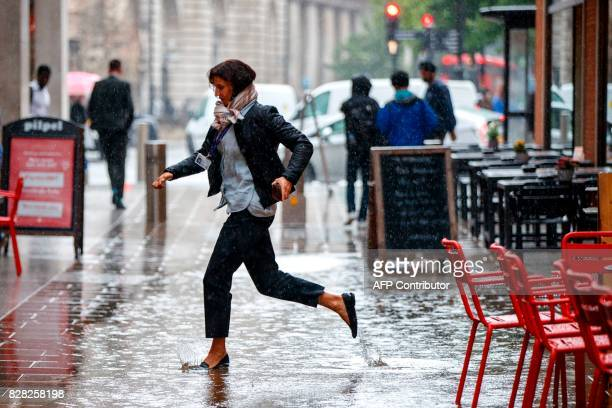 A pedestrian stands in a puddle of water as rain falls in central London on August 9 2017 / AFP PHOTO / Tolga Akmen