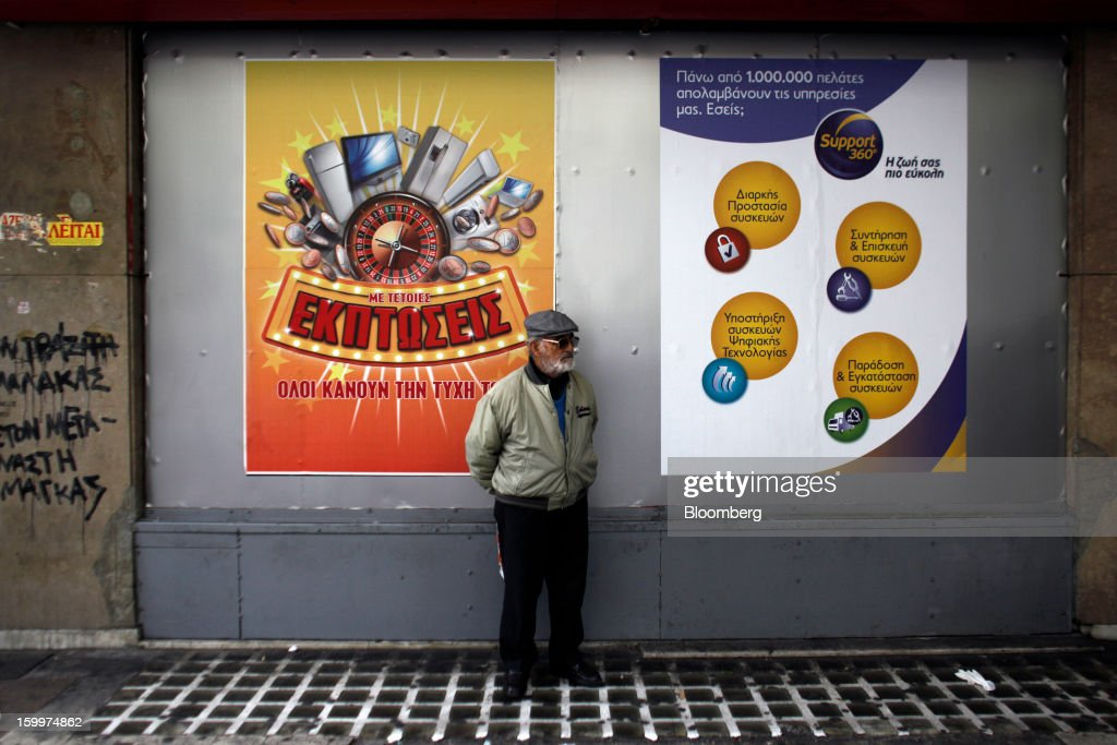 A pedestrian stands in front of an advertisement, left, for an electrical equipment retailer which reads 'Sales like these make everyone happy' in Athens, Greece, on Thursday, Jan. 24, 2013. Greece's government has implemented budget cuts and economic reforms to tame a fiscal deficit that has led to bailouts from the European Union and the International Monetary Fund. Photographer: Kostas Tsironis/Bloomberg via Getty Images