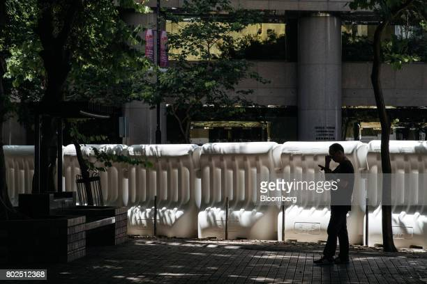 A pedestrian stands in front of water barricades near the Hong Kong Convention and Exhibition Center ahead of Chinese President Xi Jinping's arrival...