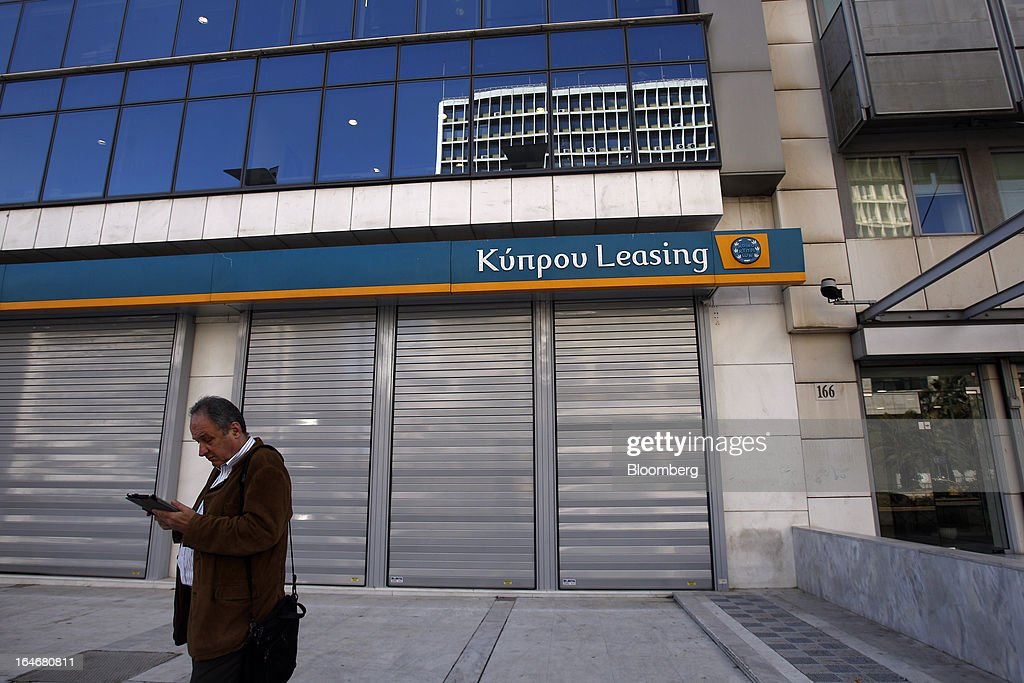 A pedestrian stands outside the shuttered facade of a closed Kyprou Leasing branch, which is a member of the Bank of Cyprus Plc group, in Athens, Greece, on Tuesday, March 26, 2013. Piraeus Bank SA acquires Greek units of Cypriot lenders for total cash consideration of EU524m, according to e-mailed statement from the Athens-based lender today. Photographer: Kostas Tsironis/Bloomberg via Getty Images