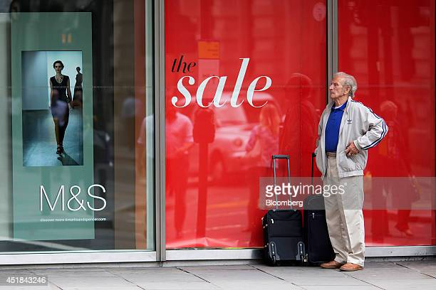 A pedestrian stands with suitcases near an advertisement for women's clothes in the window display of a Marks Spencer retail store operated by Marks...