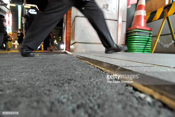 A pedestrian steps across a slight gradation on the sidewalk in front of JR Hakata Station early in the morning after the ground started sinking...