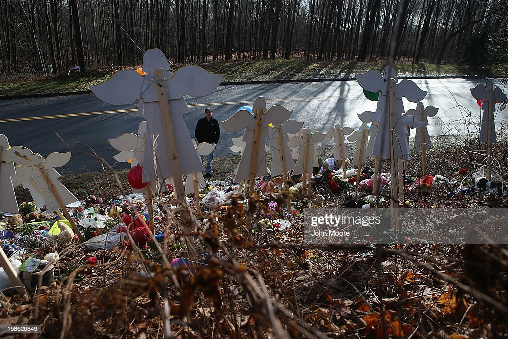 A pedestrian stops at a streetside memorial on December 21, 2012 in Newtown, Connecticut. Church bells rang out at 9:30 EST to mark the one-week anniversary of the Sandy Hook Elementary School massacre.