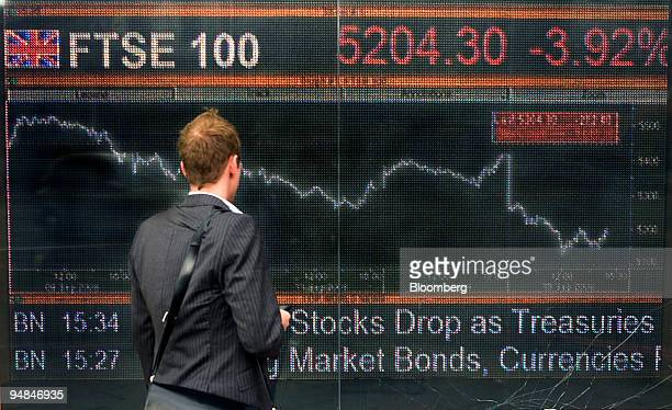 A pedestrian stops to look at a screen showing the latest FTSE 100 index in London UK on Monday Sept 15 2008 London is turning against the $450...