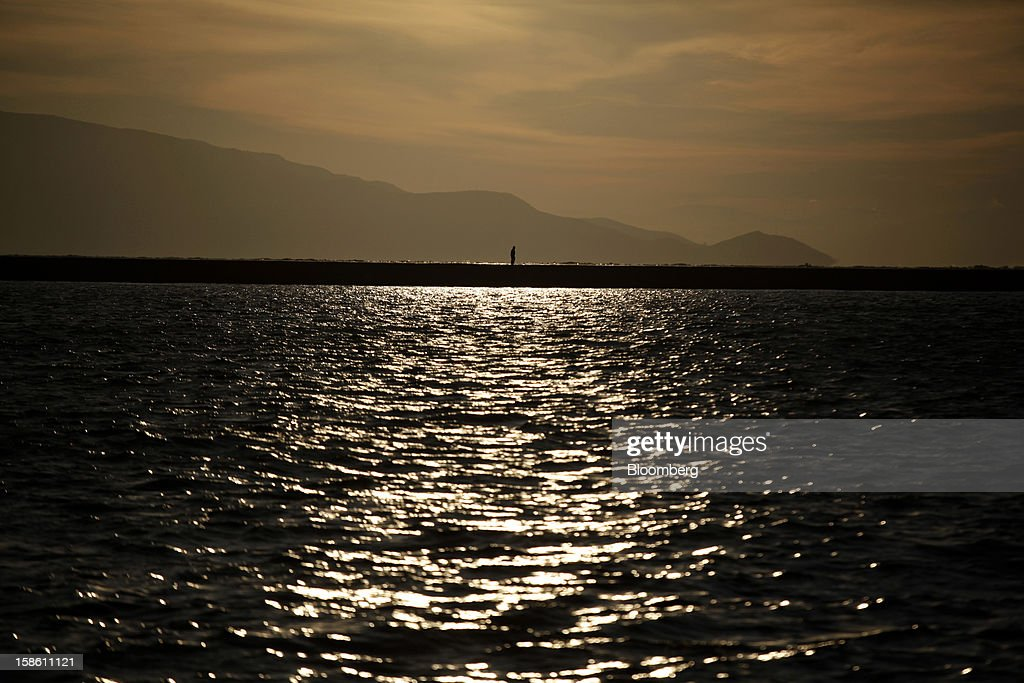 A pedestrian takes a dawn walk along the harbor breakwater back-dropped by Turkish mountains in Mytilene, on the island of Lesbos, Greece, on Saturday, Dec. 8, 2012. In recent months, Lesbos has become a hot spot for migrants as Greece struggles to cope with waves of refugees from Middle Eastern conflict even as it reels from economic crisis at home. Photographer: Kostas Tsironis/Bloomberg via Getty Images
