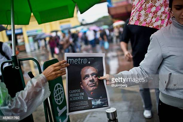 A pedestrian takes a Metro newspaper from a worker reporting the death of Brazilian presidential candidate Eduardo Campos in Rio de Janeiro Brazil on...