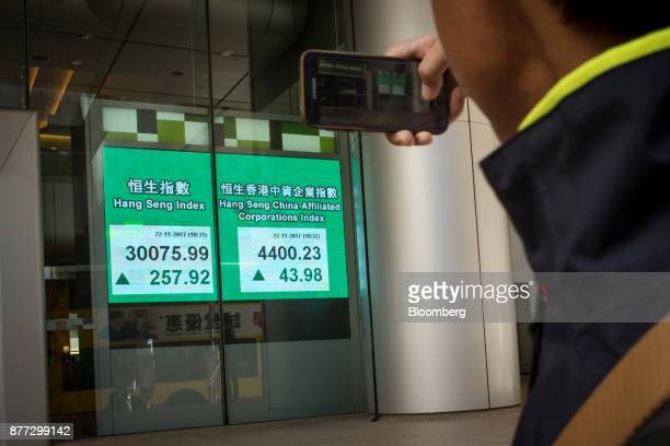 A pedestrian takes a photograph of an electronic screen displaying the Hang Seng Index left and the Hang Seng ChinaAffiliated Corporations Index in...