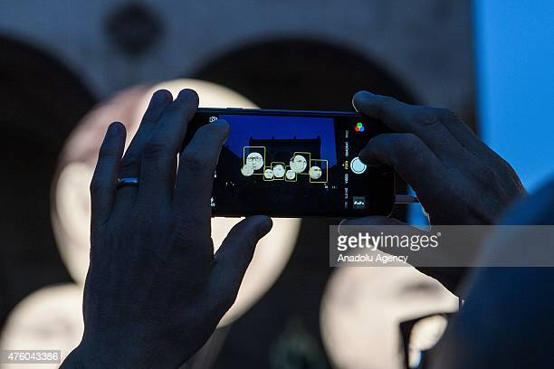 A pedestrian takes a picture with his mobile phone of balloons decorated with the portraits of Japanese Prime Minister Shinzo Abe French President...
