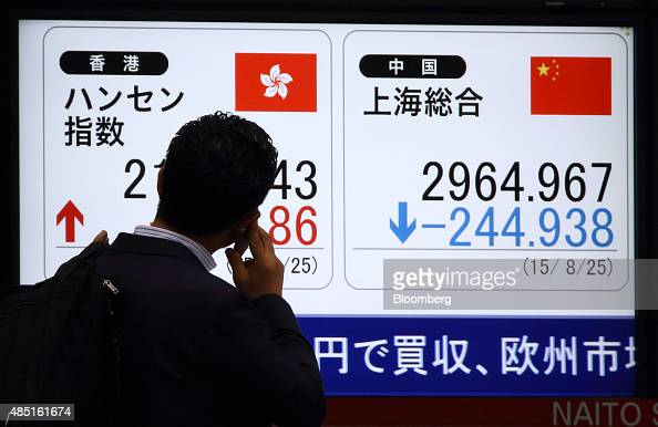 A pedestrian talking on a smartphone looks at an electronic stock board displaying the Hang Seng Index left and the Shanghai Composite Index outside...