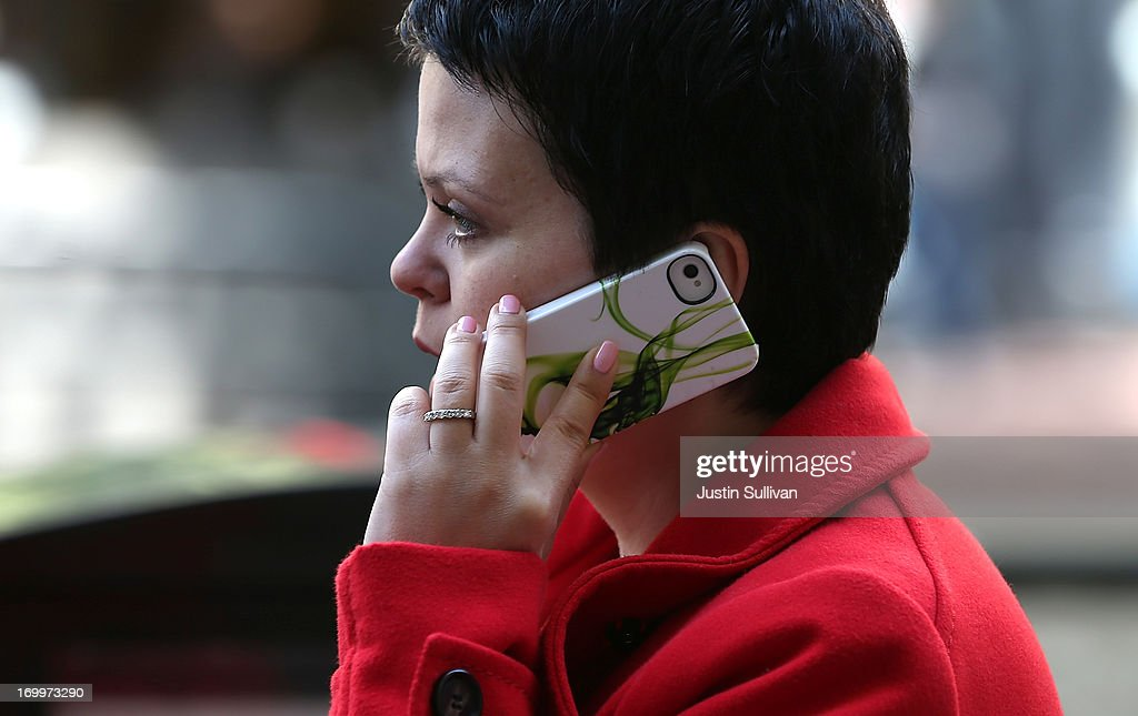 A pedestrian talks on an iPhone as she walks along Market Street on June 5, 2013 in San Francisco, California. According to a study by the Pew Internet & American Life Project, over half of American adults, or 56 percent, have smartphones, up from 35 percent two years ago.