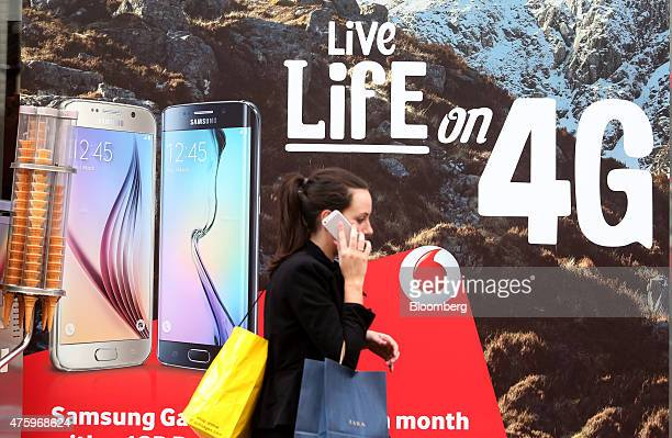 A pedestrian talks on her mobile phone device as she walks past a Vodafone advertisement outside a store operated by Vodafone Group Plc in London UK...